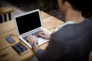 back of man at laptop