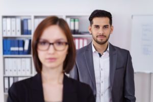 Calm businessman behind woman in office